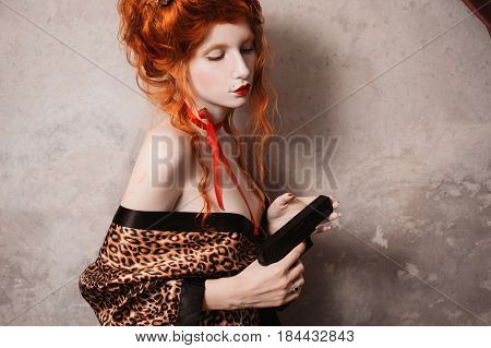 A retro woman with red hair in leopard print retro gown with a gun in his hand. Red-haired retro girl with pale skin and blue eyes with a bright unusual appearance with a red ribbon around her neck. French retro courtesan. Retro model