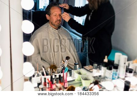 Backstage man sitting in front of mirror getting make-up.