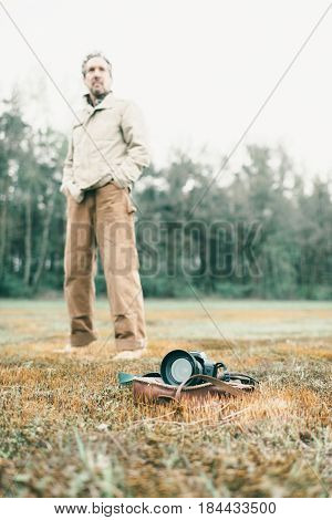 Man Standing Behind Leather Bag With Camera Lying In Field.