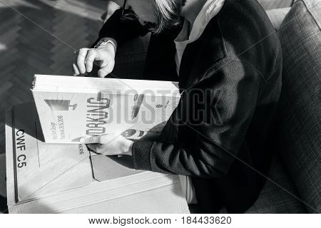 PARIS FRANCE - APRIL 24 2017: Black and white image of woman unboxing new book Living Doing Working & Enjoying: Red Dot Design Yearbook shows current award-winning products