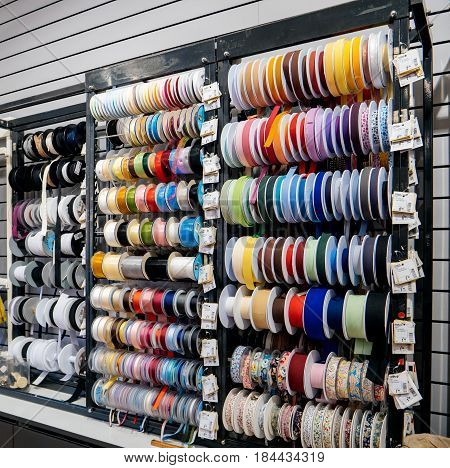 STRASBOURG FRANCE - APR 27 2017: Interior of Textile Tissue Fabric shop with multi colored and diverse accessories for sewing tools and accessories - colourful ribbons