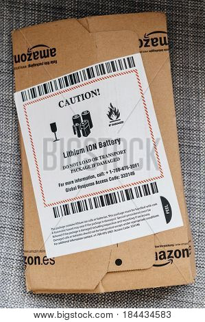 PARIS FRANCE - APR 24 2017: Amazon box with special CAUTION sign and instruction for transportation care and handling of the included Lithium Ion Li-Ion batteries cells accumulators power bank electricity generator. Amazon Inc is the an American electroni