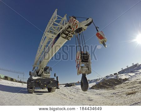 Mobile crane in work at a construction site winter. Crane on rubber wheels with raised boom