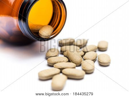 Medicine spilling out of a bottle isolated on white background Vitamin for health