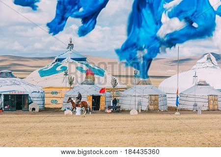 20140924_inner Mogolia,china A Mogolian Local Ride A Horse In Front Of Group Of Yurts In Mongolia ,i