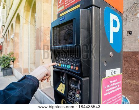 STRASBOURG FRANCE - APR 27 2017: Street scene of woman paying for the parking at the teller Parking ticket payment machine in the city - new QWERTy keyboard system being introducend in France to prevent fraud