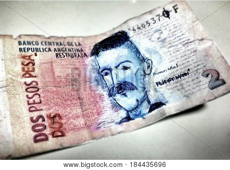 Cartoon drawn with a pen on an argentinian billet. Two argentinian pesos. Argentinian money. $2.