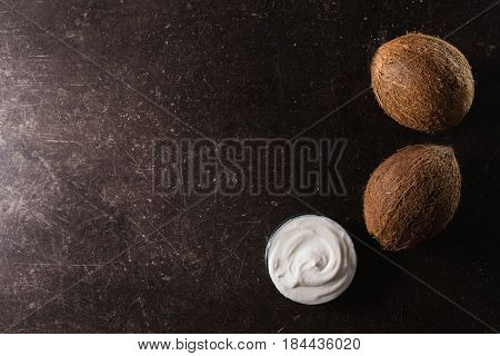 Coco nut cream coco nut milk and oil on a dark marble background. Exotic large nut. Personal care. Spa treatments. Big nut. Nut on table