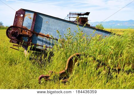 Abandoned agricultural equipment taken on forgotten landscape in a lush green field