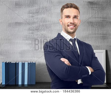 Young man and books on background