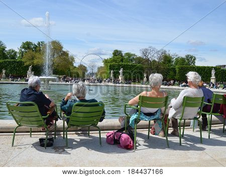 Older people resting near the fountain man woman family