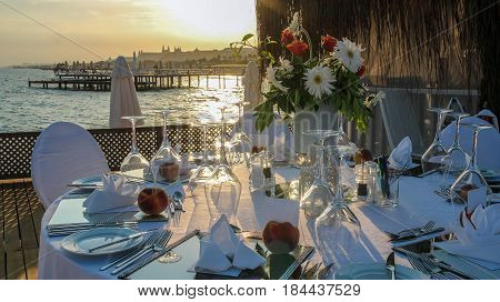 Beautiful Table Setting on Pier at Sunset. Wedding reception place ready for guests.
