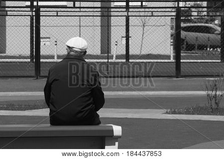 A Lonely Old Man Sits On A Bench With His Back To Us And Looks At The Sports Basketball Court. A Sym
