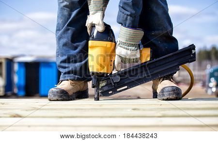 Close up of legs and feet in steel toe boots and arms of man in overalls and work gloves using an air nailer on wood boards outdoors in summer