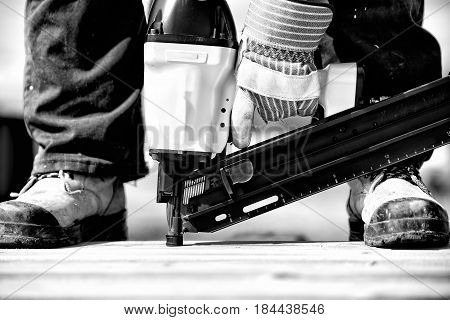 Extreme closeup of a man in steel toe work boots standing on wood boards and a gloved male hand holding an industrial air nailer in black and white