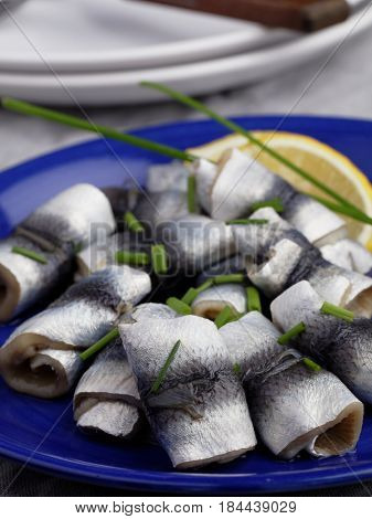 Rollmops the traditional German herring fillet rolls with green onion and lemon in a blue plate