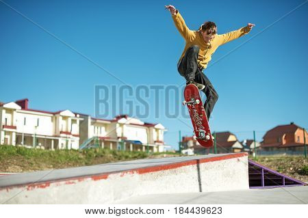 A teenager skateboarder does an ollie trick in a skatepark on the outskirts of the city On a background of houses and a blue sky poster