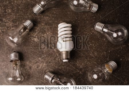 Save light. Fluorescent light bulb on a dark marble background. To save energy. Eco concept save electricity. To save planet