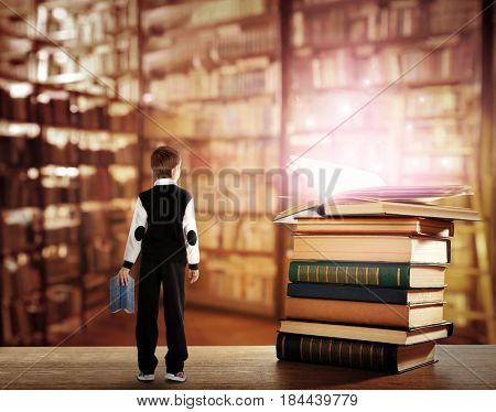 Adventure story and fairy tale. Tiny boy and books with magic glowing on table at library