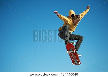 A teenager skateboarder does an ollie trick in a skatepark on the outskirts of the city On a background of blue sky gradient poster