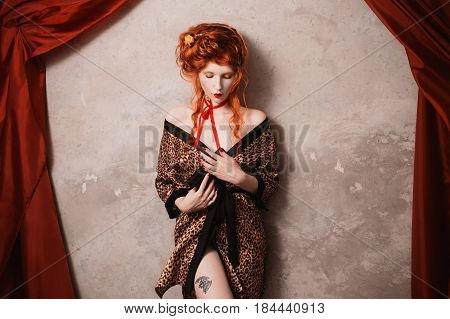 A vintage woman with red hair in leopard print vintage gown with a gun in his hand. Red-haired vintage girl with pale skin and blue eyes with a bright unusual appearance with a red ribbon around her neck. Vintage background French courtesan. Vintage model