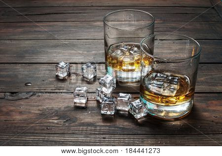 Two glasses of whiskey with ice cubes served on wooden planks. Vintage countertop and a glass of hard liquor.