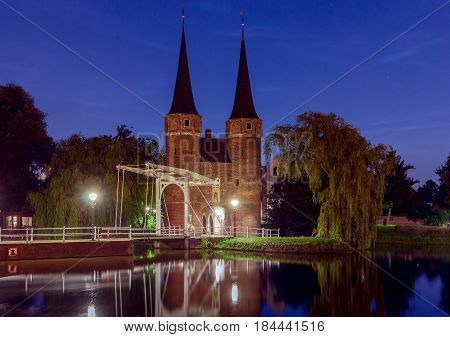 Eastern Gate with the white draw bridge, along Delftse Schie canal at night, Delft, Holland, Netherlands.
