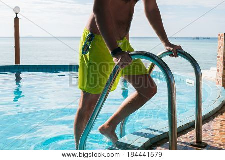 Young man in outdoor pool holds on handrails