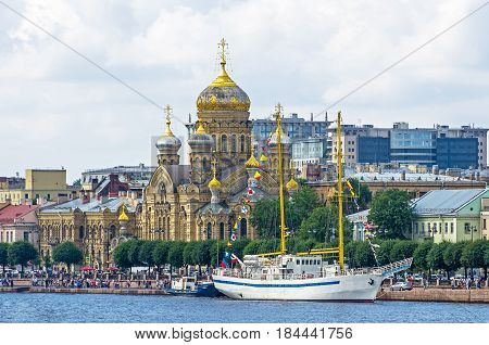 Uspensky temple on the bank of the Neva river and a sailboat near the embankment