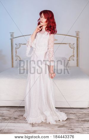 Beautiful royal girl with red hair and natural make-up and pale skin. A royal woman in a white royal dress renaissance. Royal model posing in studio. The unusual appearance. The royal bride in the bedroom