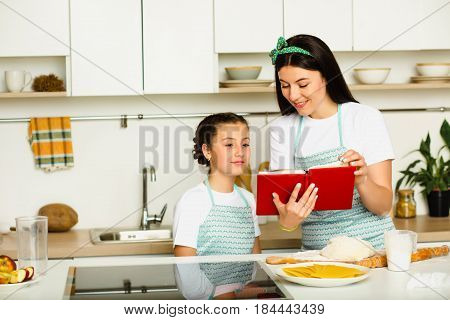 Mother teaches her daughter how to cook food, standing at white kitchen, laughing and looking in the book of recipes. Family leisure at home