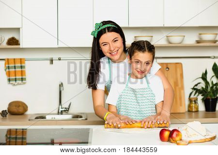 Mother and daughter preparing food, rolling out dough With rolling pin. Staying at home in your kitchen, laughing and looking at the camera. Family leisure at home