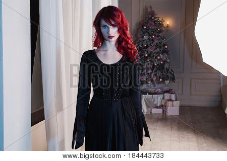 Beautiful halloween girl with red hair and natural make-up and pale skin. A halloween woman in a black retro halloween dress. Halloween model posing in studio. The unusual appearance. Insidious wicked witch halloween woman.