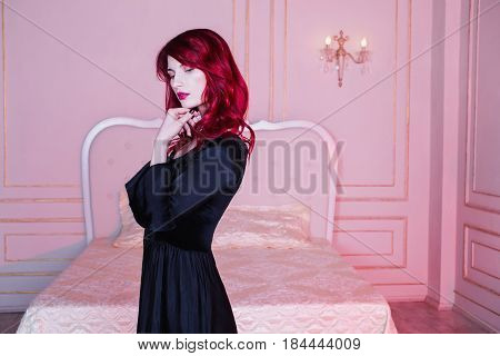 Beautiful elegant girl with red hair and natural make-up and pale skin. A elegant woman in a black elegant retro dress. Model posing in studio. The unusual appearance. Insidious wicked witch elegant woman.