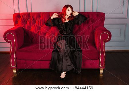 Beautiful stylish girl with red hair and natural make-up and pale skin. A stylish woman in a black retro stylish dress sitting on a red couch. Model posing in studio. The unusual appearance. Insidious wicked witch stylish woman.