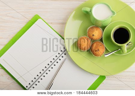 Coffee with milk muffins and notepad on wooden background. Selective focus.
