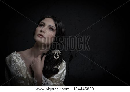 portrait of woman in vintage dress on dark background with texture of a painting of the Renaissance