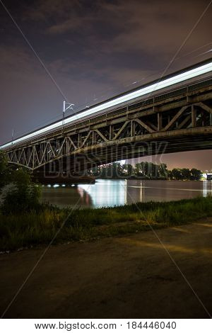 Bridge by night  Train bridge with lights and dark sky, National Stadium by Vistula river  Illuminated railway bridge in Warsaw, Poland  Europe