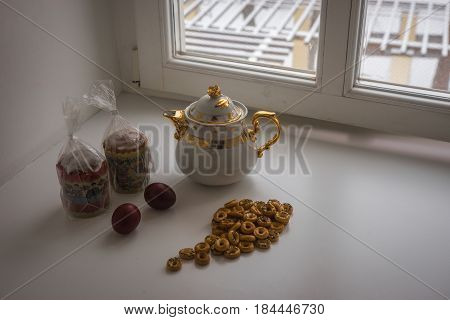 Scenic view of still life with two Easter cakes eggs bagels and a teapot on a sill and trees covered with snow seen through the open window
