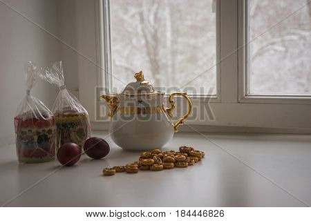 Still Life With Two Easter Cakes, Eggs, Bagels And A Teapot On A Sill And Trees Covered With Snow Se