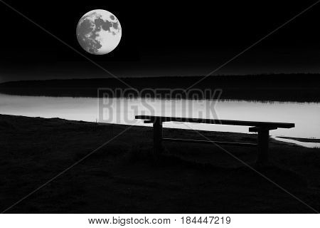 Conceptual view of the expectations of the bench under a full moon. Landscape fullmoon over horizon on sea. Panorama with the lun: grand mystical fantastic view.