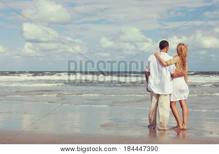 Instagram style photograph of romantic young man and woman couple embracing on a beach