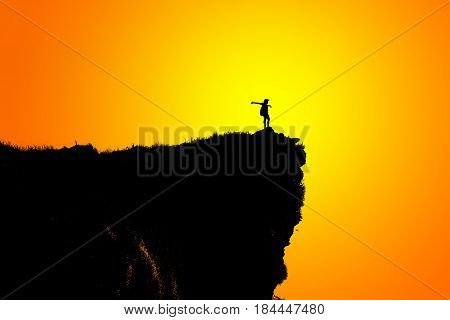 Black silhouette on orange and yellow background of woman tourist standing arms outstretched happy with success on peak mountain near the cliff at Phu Chi Fa Viewpoint Chiang Rai Thailand