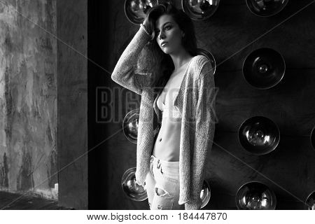 Black And White Portrait Of A Girl In Underwear And A Cardigan, Standing Against The Wall With Lamps