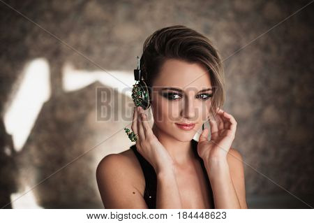 Happy woman. Lovely happy girl with tanned skin and white hair listening to music on headphones. Female beauty happy portrait of a beautiful makeup. Enjoying good music and be happy. Happy girl.