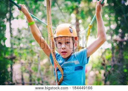 frightened boy in high wire park. kid ready to zip line flight in adventure park. zip lining. fear of heights