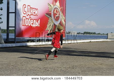 Volgograd Russia - May 09 2016: A little girl in a military garrison cap runs along the embankment in the background of the banner (translated from the Russian