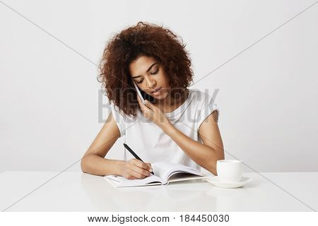 Young gorgeous hipster african woman talking business ideas on cell phone, taking orders on her new designer apparel line. Buying a ticket for her future trip offline. White background, copy space.