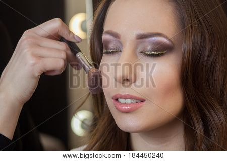 Make-up Artist Puts Powder On The Face Of A Beautiful, Brunette Girl In The Beauty Salon. Profession