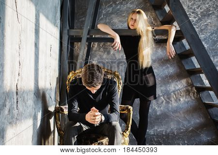A young man with problem and young blonde woman with long hair. Problem and difficulties in relations. Difficult situation in life. Conceptual photography. Actor play problem. Hard shadows. Show feelings. Hide problem